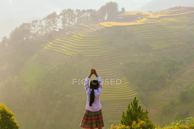 Mujer de pie frente a campos de arroz en terrazas al atardecer, Mu Cang Chai, Vietnam - foto de stock