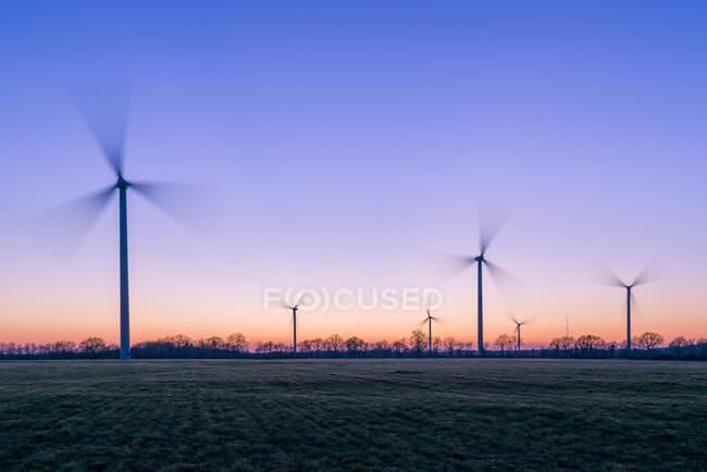 Silhouette des éoliennes au coucher du soleil, France — Photo de stock