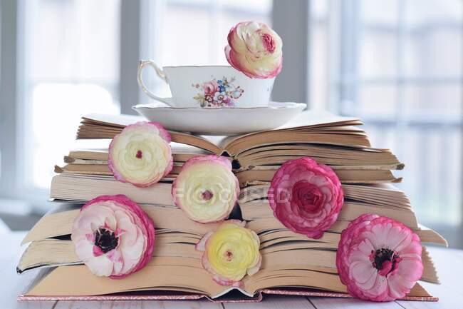 Чашка чая на стопке книг и цветов — стоковое фото