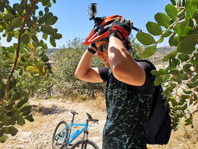 Ciclista que se pone su casco de ciclismo con cámara portátil, Malta - foto de stock