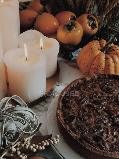 Coffee and chocolate tart next to candles and vegetable display — Stock Photo