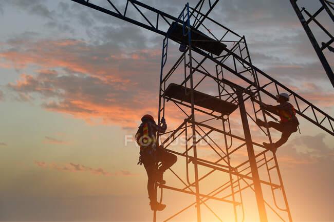 Силуэт двух строителей, взбирающихся на строительные леса, Таиланд — стоковое фото