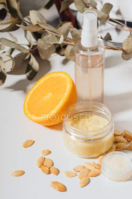 Lip balm and moisturisers with argan seeds, orange and dried leaves - foto de stock