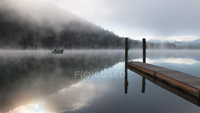 Silueta de dos personas en un barco pescando en la niebla de la mañana, Lemolo Lake, Umpqua National Forest, Oregon, EE.UU. - foto de stock