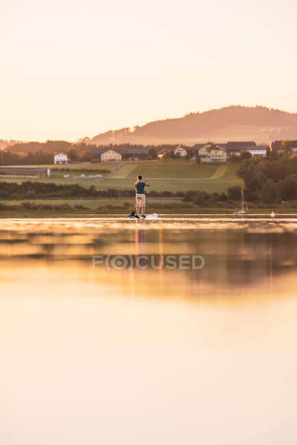 Giovane donna in piedi paddleboarding al tramonto, Lago Wallersee, Flachgau, Salisburgo, Austria — Foto stock