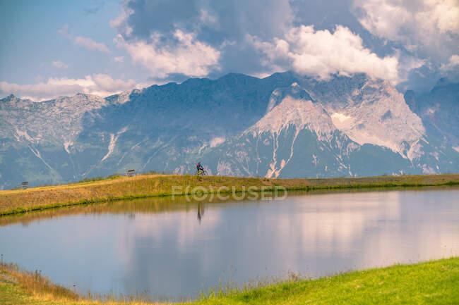 Man cycling past a lake in the Austrian Alps, Saalbach, Zell am See, Salzburg, Austria — Stock Photo