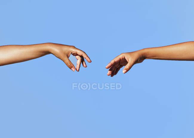 Dos brazos de mujer extendidos extendiéndose uno hacia el otro - foto de stock