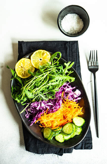 Red cabbage, rocket, carrot and cucumber with salt and lemon — Stock Photo