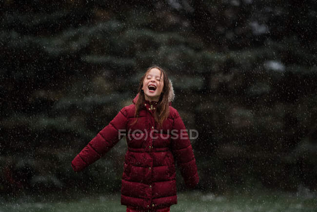 Happy girl standing outdoors in the snow, USA — Stock Photo