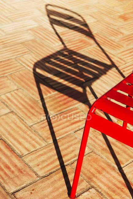 Sombra de uma cadeira de metal vermelho num terraço com azulejos, Portugal — Fotografia de Stock