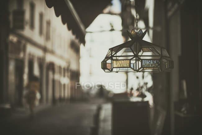 Lámpara de vidrio colgada en el mercado vintage con mujer en la distancia, España - foto de stock