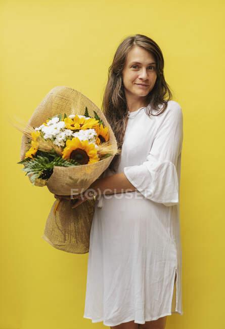 Беременная женщина держит букет цветов — стоковое фото