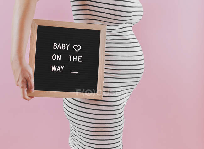 Беременная женщина объявляет о своей беременности, используя табличку с надписью