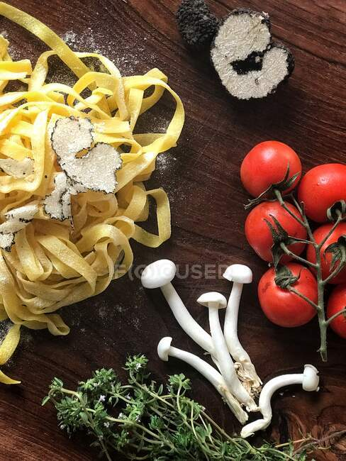 Fresh tagliatelle pasta with truffle shavings, mushroom, tomato and thyme — Stock Photo