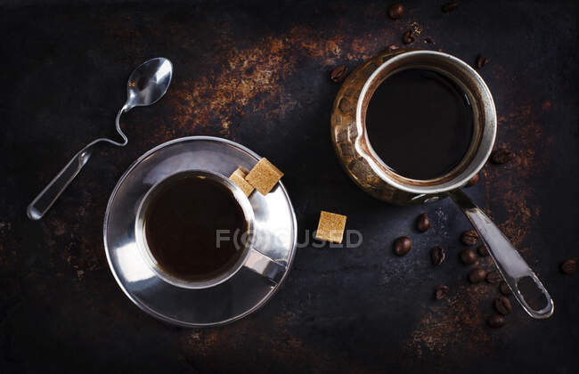 Cup of black coffee with sugar cubes and a cezve — Stock Photo