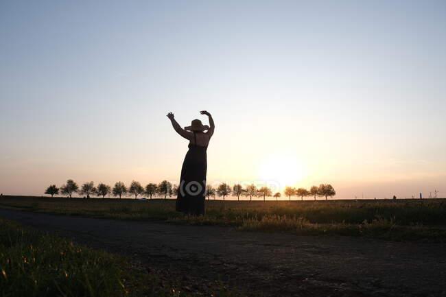 Silueta de una mujer de pie en un campo al atardecer bailando, Francia - foto de stock