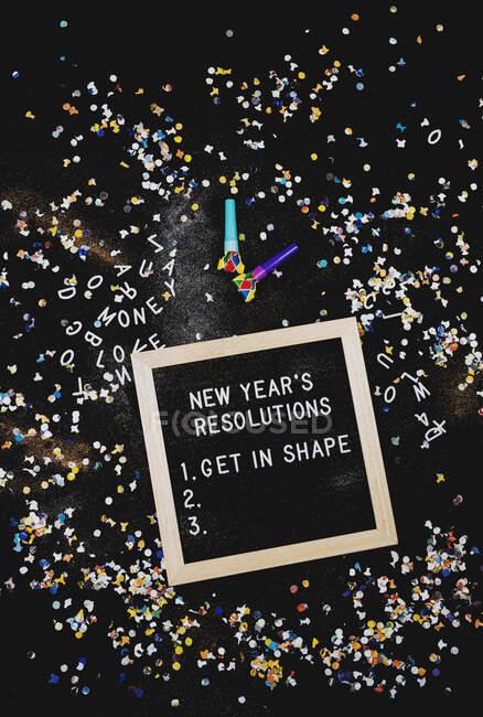 Новий рік Резолюції на дошці з написами, оточені конфетті і партійними душогубами — стокове фото