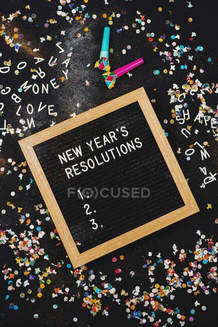 Risoluzioni di anno nuovo su una cartolina circondata da coriandoli e festaioli — Foto stock