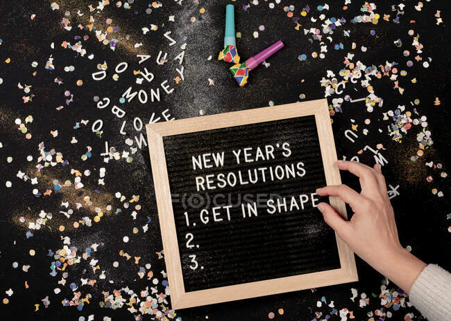 Person setting New Year's Resolutions on a letterboard surrounded by confetti and party blowers - foto de stock