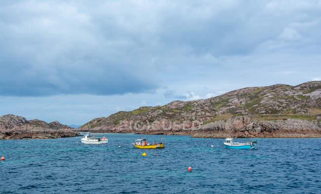 Tres barcos de pesca anclados en el mar de la Isla de Mull, Hébridas Interiores, Escocia, Reino Unido - foto de stock