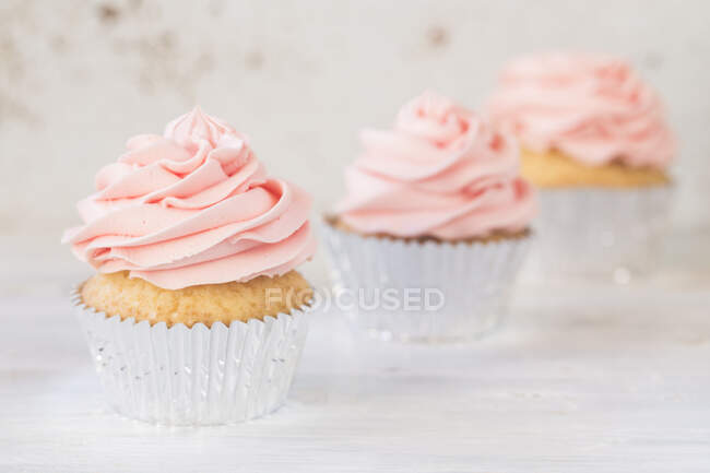 Three cupcakes with buttercream icing — Stock Photo