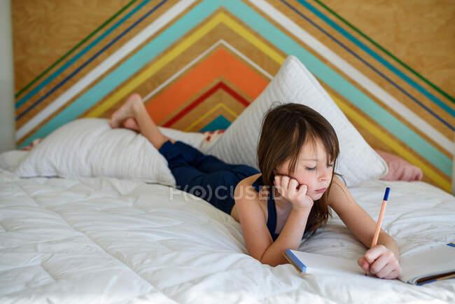 Ritratto di una ragazza sdraiata sul letto a fare i compiti — Foto stock