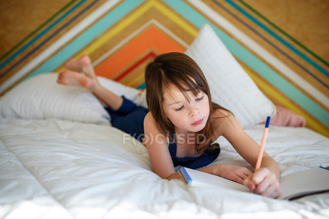 Portrait of a girl lying on her bed doing her homework — Stock Photo