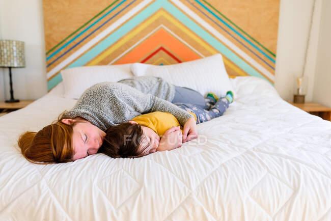Madre e figlia dormire e abbracciare sul letto — Foto stock