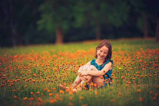 Happy girl sitting in a meadow with wildflowers laughing, USA — Stock Photo
