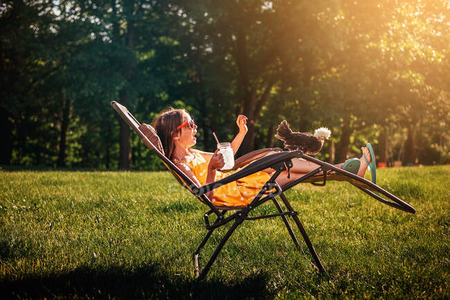 Happy girl sitting in the garden with a chicken on her chair — Stock Photo