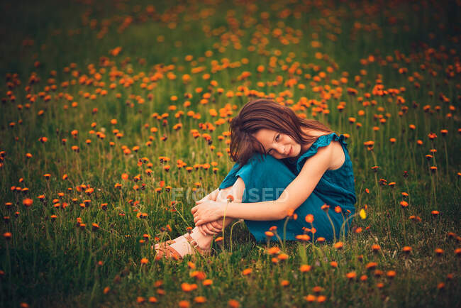 Happy girl sitting in a meadow with wildflowers, USA — Stock Photo