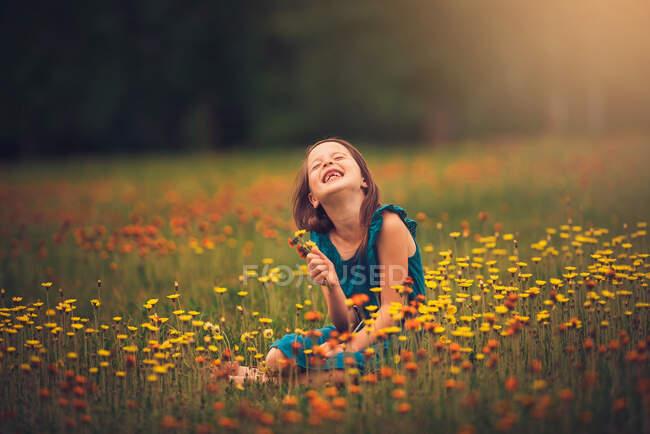 Щаслива дівчина, що сидить на лузі і збирає польові квіти (США). — стокове фото
