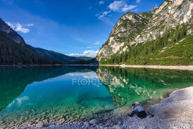 Mulher sentada ao lado do Lago Braies tirar uma foto, Tirol do Sul, Itália — Fotografia de Stock