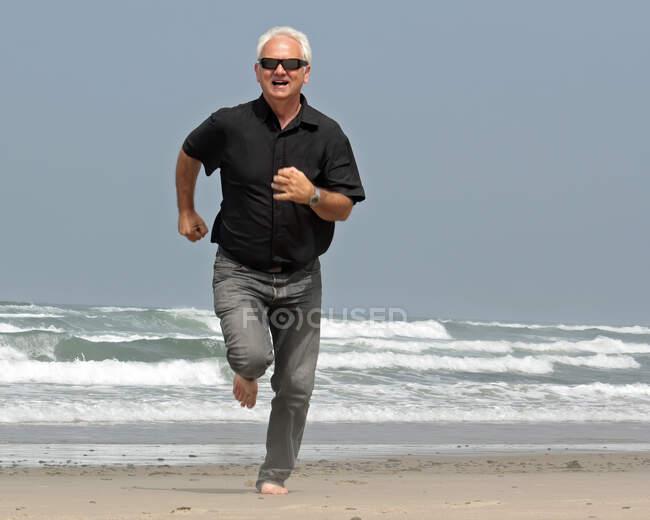 Maduro homem correndo na praia, Oregon, EUA — Fotografia de Stock