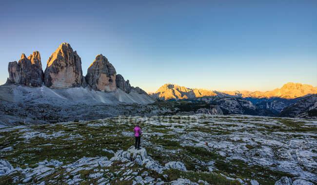 Mujer mirando Sunrise, Tre Cime di Lavaredo, Dolomitas, Tirol del Sur, Italia - foto de stock