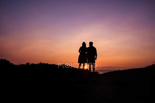 Silueta de una pareja viendo atardecer sobre el océano, Maui, Hawaii, EE.UU. - foto de stock