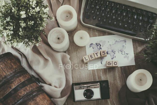 Вигляд друкарської машинки, аналогової камери, карти світу та свічки на столі. — стокове фото