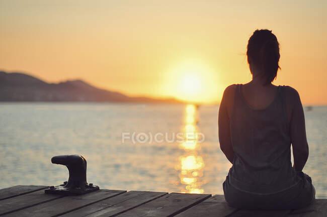 Vista posteriore di una donna seduta su un molo guardando il tramonto, Maiorca, Baleari, Spagna — Foto stock