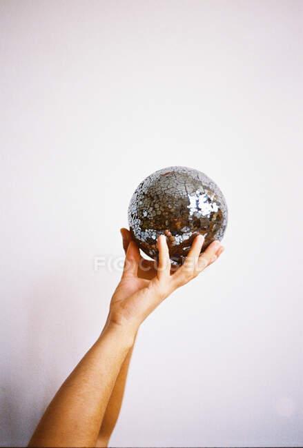 Mão humana segurando uma glitterball — Fotografia de Stock