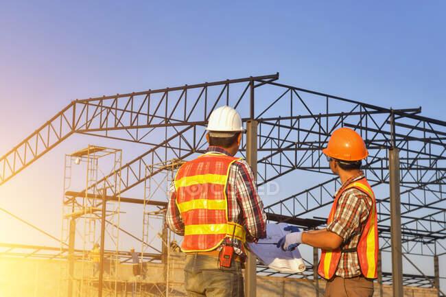Dois trabalhadores de construção em um canteiro de obras olhando para os planos, Tailândia — Fotografia de Stock