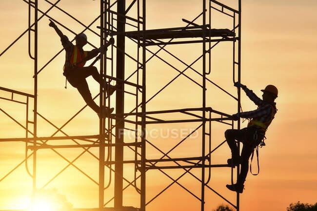 Silueta de dos trabajadores de la construcción escalando andamios en un sitio de construcción, Tailandia - foto de stock