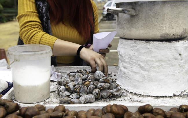 Mujer recogiendo castañas asadas en un puesto callejero, Sevilla, España - foto de stock