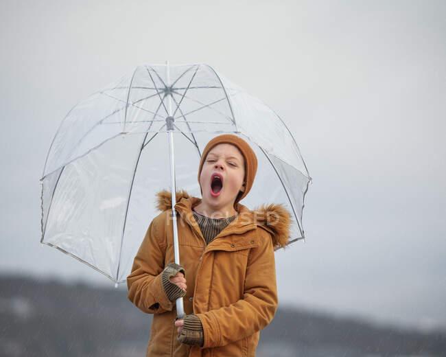 Menino segurando um guarda-chuva bocejando, Bedford, Nova Escócia, Canadá — Fotografia de Stock