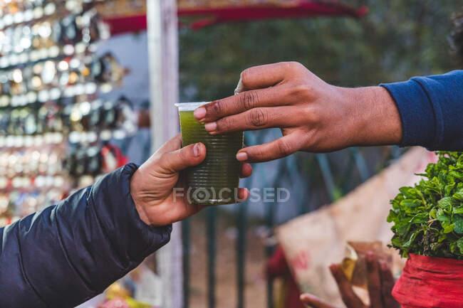 Hombre que compra una bebida de limón y menta en un puesto de mercado, Delhi, India - foto de stock