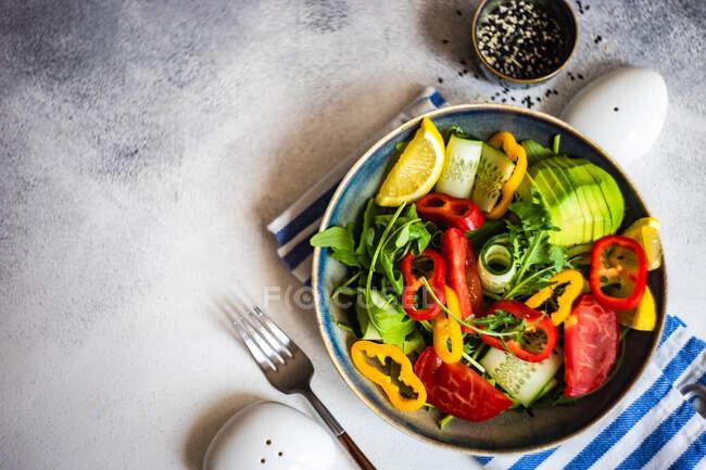 Здоровый овощной салат с арагулой, авокадо и кунжутом на бетонном фоне с копировальным пространством — стоковое фото