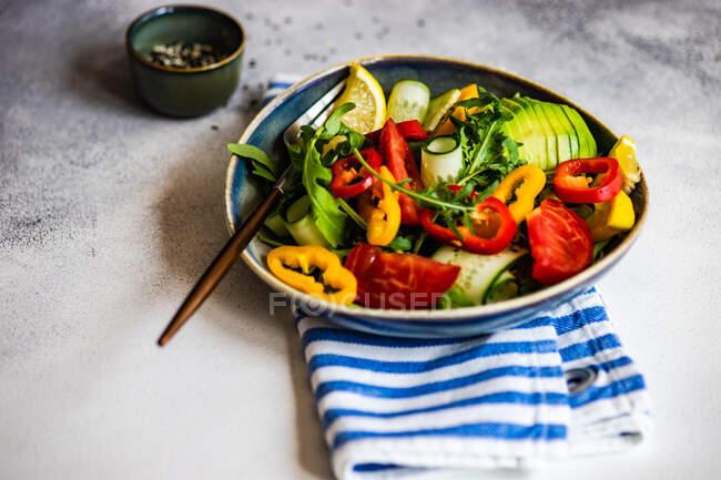Ensalada de rúcula con aguacate, pimienta, tomate y semillas de sésamo - foto de stock