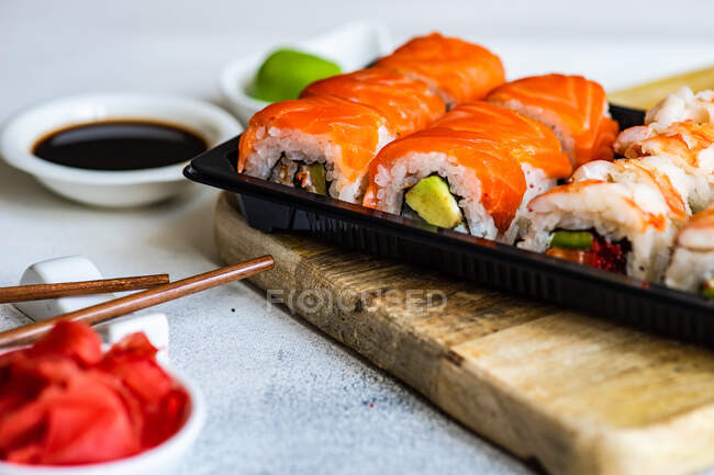 Salmon and prawn maki rolls with pickled ginger, wasabi, soy sauce and chopsticks — Stock Photo