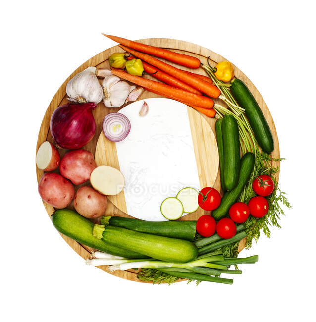 Fresh fruit and vegetables on a circular chopping board — Stock Photo