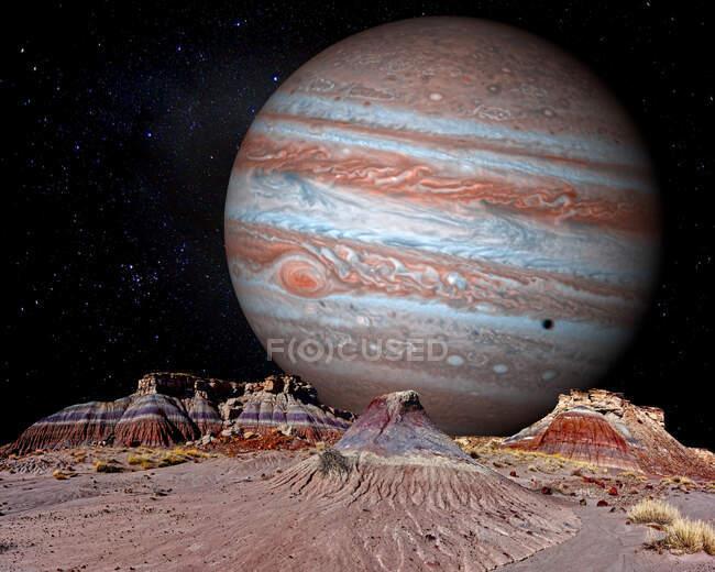Imagen conceptual de Júpiter elevándose sobre el bosque Jasper, Parque Nacional Bosque Petrificado, Arizona, EE.UU. - foto de stock