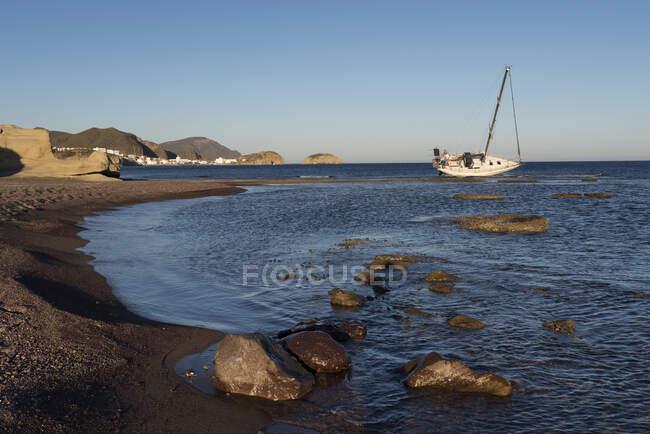 Лодка на якоре у пляжа во время отлива, пляж Лос-Эскуллос, Лос-Эскуллос, Кабо-де-Гата, Альмерия, Андалусия, Испания — стоковое фото